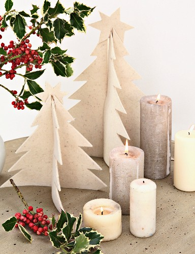 Hand-made felt Christmas trees, lit candles and sprigs of holly on concrete table