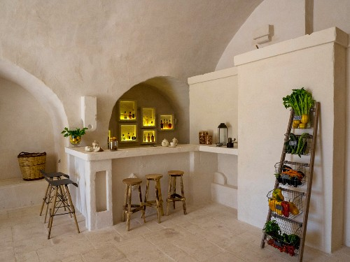 Illuminated niches above masonry counter and bar stools next to baskets of vegetables on ladder shelves