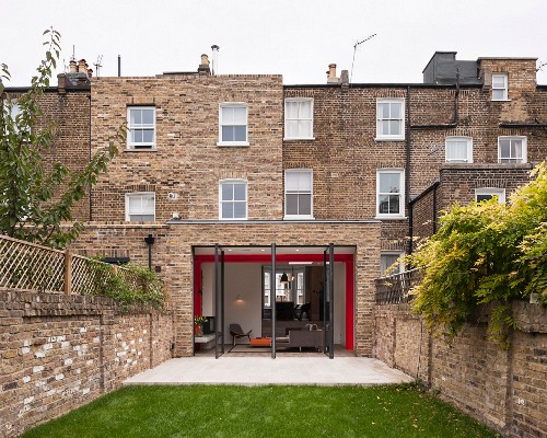 View from courtyard; traditional English brick house with open terrace doors and extension
