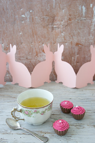 Spring herb tea in vintage cup, chocolates and paper Easter bunnies