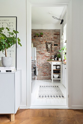 View into kitchen with brick wall