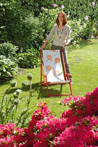 Woman with revamped deckchair in garden