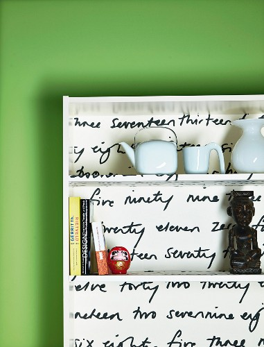 DIY shelves lined with printed fabric against green wall