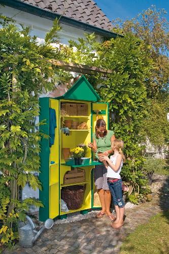 Gardening utensils in DIY garden cupboard: woman and girl planting up pots
