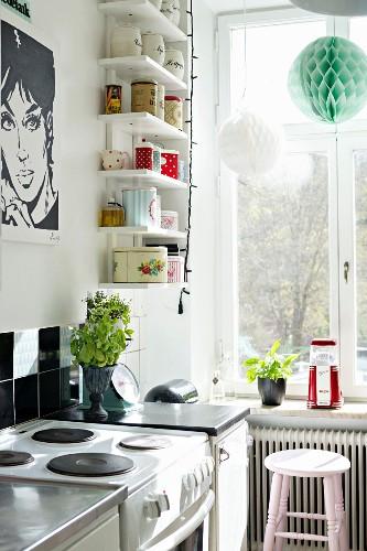 Black and white Pop-Art poster and vintage storage jars on white shelves in corner of kitchen