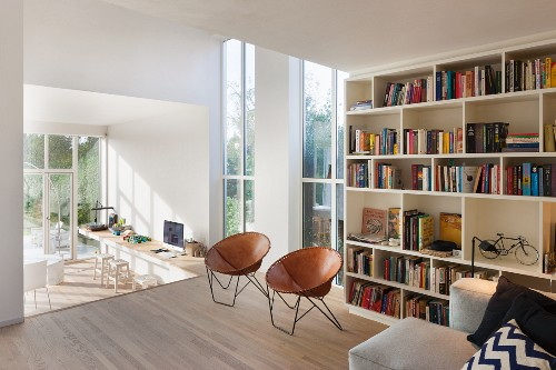 Tall windows and bookcase in living area with counter in sunken area in background