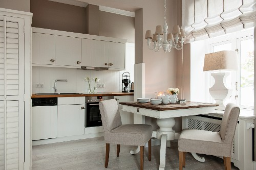 Dining table for two with upholstered chairs below window in white fitted kitchen