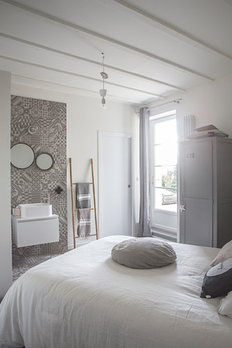 White bedspread on bed and washstand against ornate grey wall-tiles in restored bedroom
