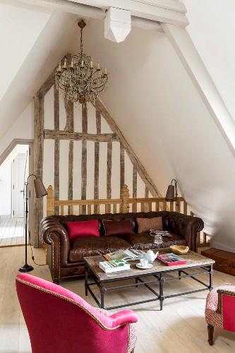 Loungebereich im Dachgeschoss mit pinkfarbenem Sessel und braunem Ledersofa