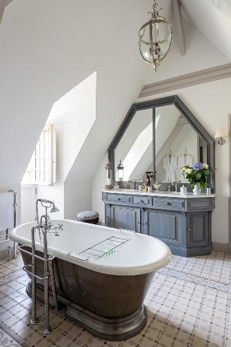 Freistehende nostalgische Badewanne mit Standarmatur auf Fliesenboden, massgefertigter Waschtisch mit grauem Unterschrank im Dachgeschoss