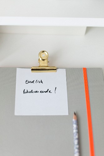 Note attached to notebook with clip