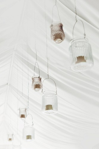 Festive arrangement of candle lanterns hung from white tent ceiling for wedding