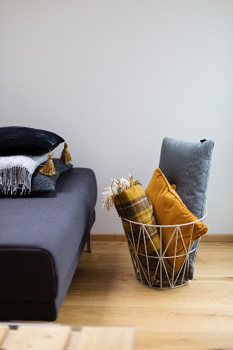 Cushions and blanket in wire basket next to sofa