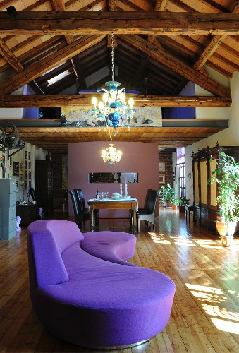 Curved purple sofa in loft apartment with wooden roof structure, lit chandeliers and dining area below gallery in background