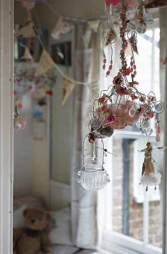 Tealight holders hung from wire frame decorated with glass pendants and figurines