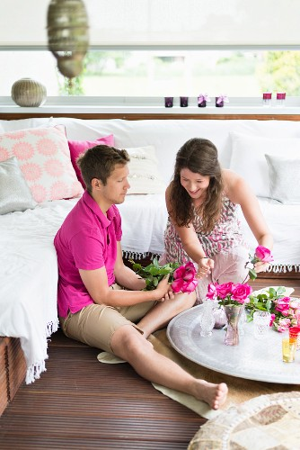 Couple sitting on floor of balcony decorated in Oriental style