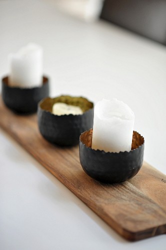 Candles in metal bowls on wooden board