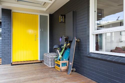 Überdachter Eingangsbereich mit gelber Haustür und grauem Sichtmauerwerk, Holzterrasse und diverse Skateboards in Holzkiste gestapelt