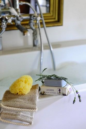 Toiletries, sponge and lavender soap on edge of bathtub