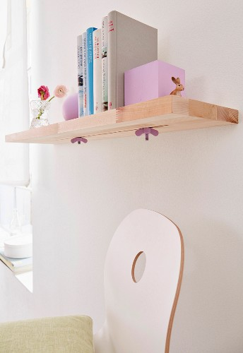 A homemade shelf made of wooden boards stuck together with sliding book ends