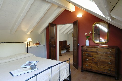 Antique chest of drawers and red wall in attic bedroom