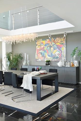 Black furniture below gallery in modern dining room