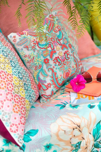 Colourful patterned cushions on seat
