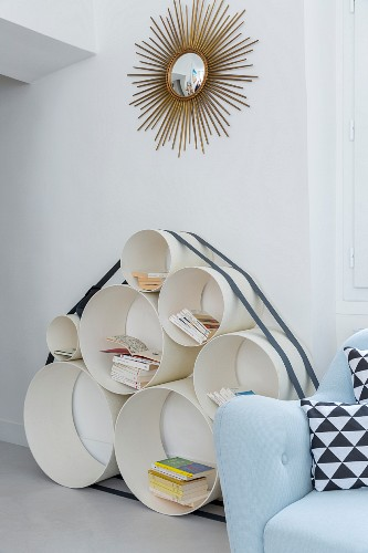 Shelves made from pipes of various diameters below gilt sunburst mirror