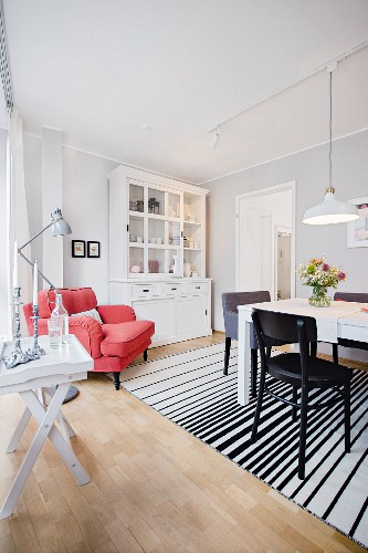 A modern dining room with a dresser, a reading corner and a striped rug