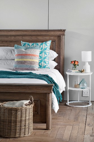 Old wooden bed with profiled headboard and foot and delicate modern bedside table