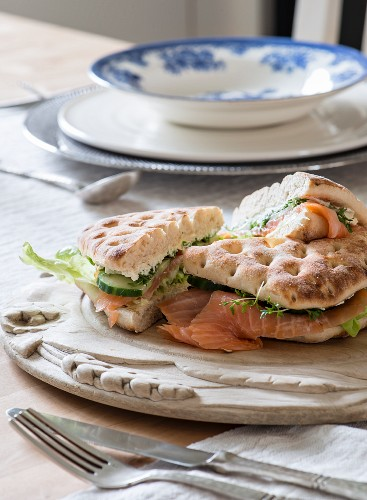 Flatbreads filled with salmon and cucumber on wooden board