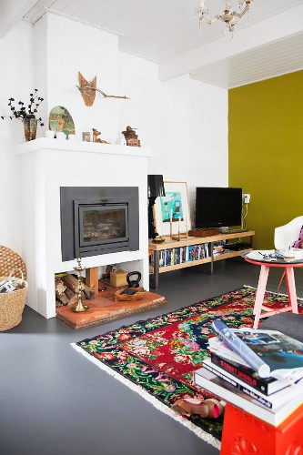Yellow wall and multicoloured rug in colourful living room