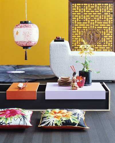 Low Oriental table, floor cushions, modern lounger and yellow wall
