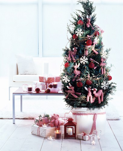 Presents under small potted conifer decorated with red and white gingham animals and red baubles