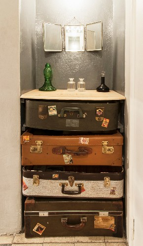 Various glass vessels on wooden surface on top of vintage suitcases stacked in niche