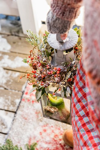 Woman carrying lantern decorated with twigs and berries