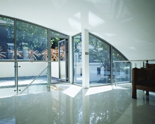 Modern living room under a barrel roof with reflective tiled floor in front of bank of windows