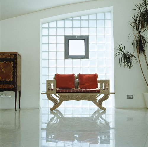 Antique, English bench with red cushion in front of a glass brick wall and reflective tile floor