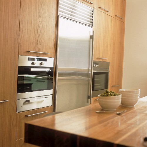 A stack of bowls on a wooden work surface in a kitchen with fitted cupboards and appliances