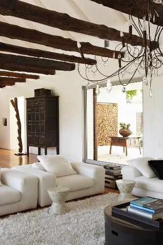 Ethnic style in spacious house - simple, modern sofa set and romantic chandelier below ceiling beams of unworked logs