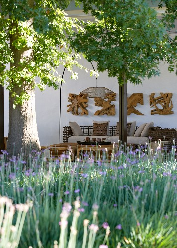 Sunny mood - seating area with designer lamp and wood sculptures, Tree and flowerbed in foreground