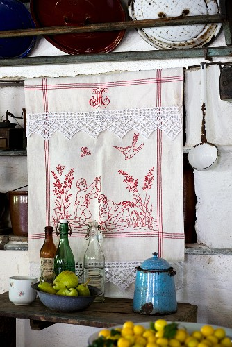 Detail of kitchen; embroidered tea towel in front of niche below vintage pan lids on wall rack