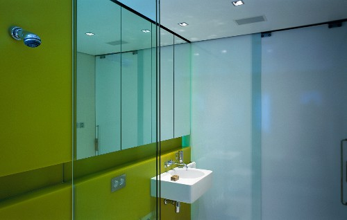 Bathroom with sink, mirror, yellow glass wall & opaque glass wall