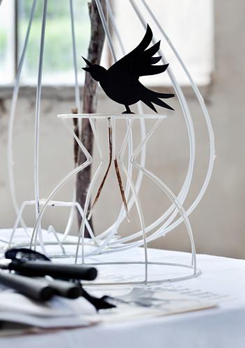 Black bird ornament on white-painted metal frame