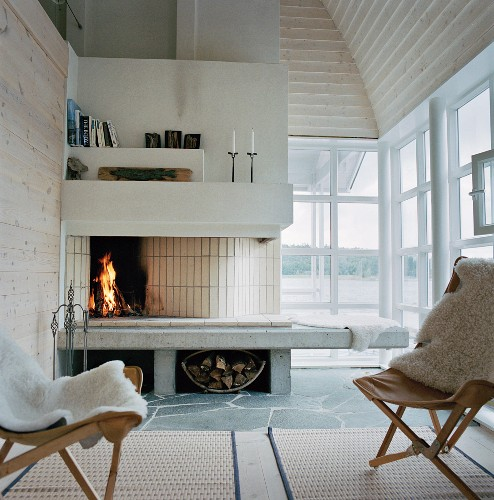 Armchair with white animal hide in front of an open fireplace