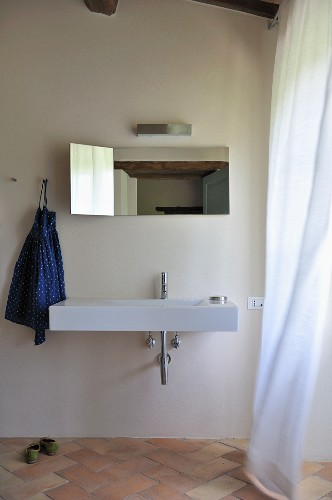 Minimalist bathroom with designer sink and mirror