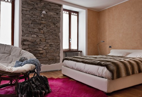 Bedroom in warm earthy shades with framed, rustic stone wall and animal-skin-patterned throw on bed
