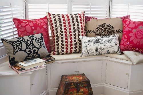 Colourful, patterned scatter cushions on window seat with integrated cupboards in bay window