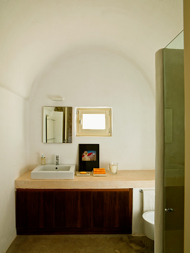 Minimalist bathroom with barrel vault ceiling - simple washstand against wall below small window
