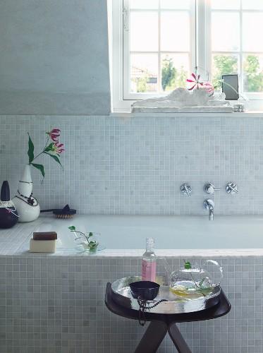 Bathroom spa - side table with bath essences in front of bathtub